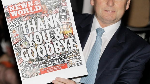 In this July 9, 2011 photo, News of the World tabloid newspaper editor Colin Myler poses with a front page of the last edition. The phone hacking scandal led the publisher, Rupert Murdoch's News International, to close the paper permanently.