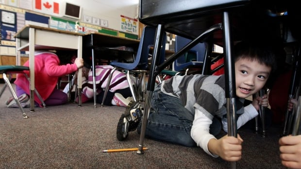 Grade one student, six-year-old Joseph Kim, takes cover under his desk during an earthquake drill at Hollyburn Elementary School in West Vancouver, B.C., on Wednesday January 26, 2011.