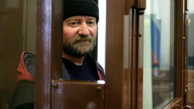Paul Ruzycki  stands in a defendant's cage at a Murmansk district court in Murmansk, Russia. He and Canadian Alexandre Paul face charges of hooliganism in connection with their protest of a Russian oil rig.