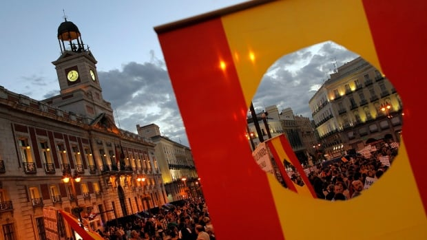 Protestors are seen through a Spanish flag during a demonstration against corruption on Oct. 5. Spain has officially emerged from recession after two years, but unemployment is still 26.3 per cent.