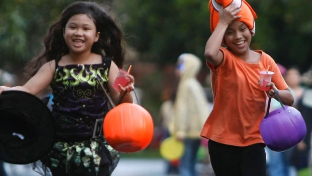 Children make the rounds of the houses at a subdivision at the financial district of Makati city in the Philippines.