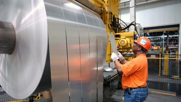 An Alcoa employee inspects finished rolls of aluminum as they come off the last stage of the production line.