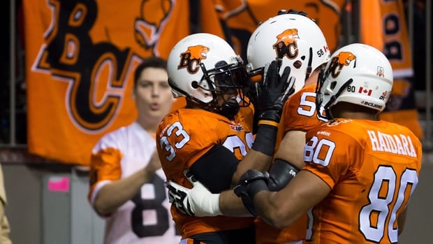 B.C. Lions' Andrew Harris, from left to right, Steve Myddelton and Seydou Junior Haidara celebrate after Harris rushed for a touchdown against the Calgary Stampeders on Friday.