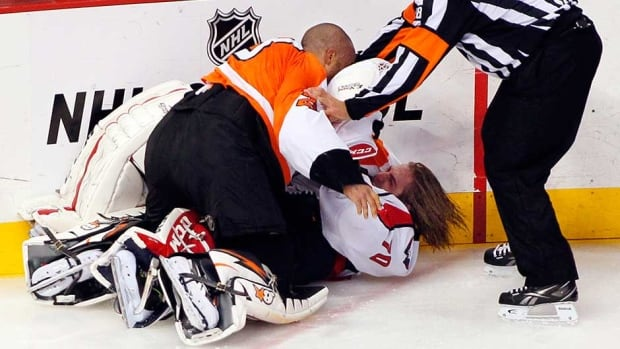 Linesman Francois St. Laurent, right, tries to pull Philadelphia Flyers goalie Ray Emery, top, off of Washington Capitals goalie Braden Holtby during a melee in the third period on Friday in Philadelphia.
