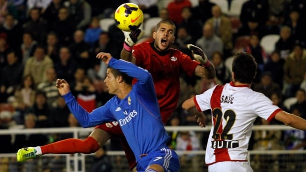 Real Madrid's Cristiano Ronaldo, left, from Portugal, vies for a high ball with Rayo Vallecano's goalkeeper Ruben Martinez, centre top, and Saul Niguez, right. Ronaldo scored twice in Real Madrid's 3-2 victory.