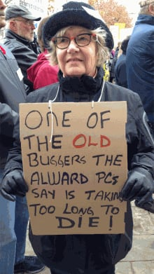 Pension reform protester carrying sign at legislature protest