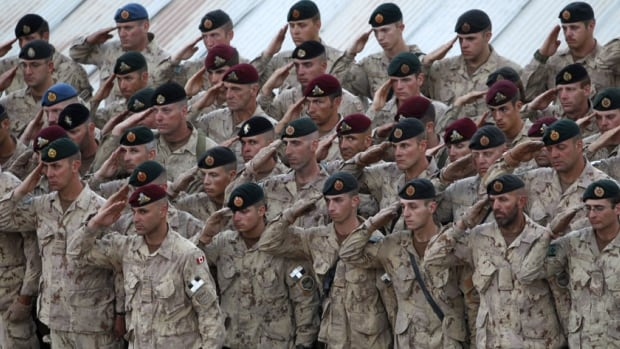 "Canadian soldiers, including those from the 1st Battalion, Royal 22e Regiment, salute during a ceremony for fallen comrades at forward operating base Masum Ghar in Kandahar province in southern Afghanistan. A new study says Canadian veterans ""significantly"" more likely to die from suicide than the average population."