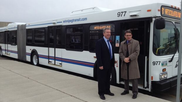 City Coun. Brian Mayes and Transit's Dave Wardrop stand near one of the articulated buses on Friday.