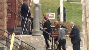 Genevieve Cormier's family carrying urn at funeral