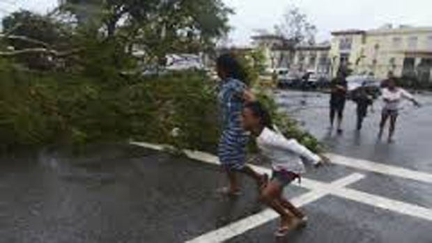 Residents rush to safety during strong winds brought by Typhoon Haiyan that hit Cebu city.