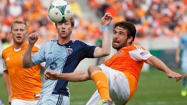 Houston Dynamo defender Mike Chabala, right clears the ball before Sporting KC midfielder Jacob Peterson, right, can get possession during the first half on Saturday in Houston.