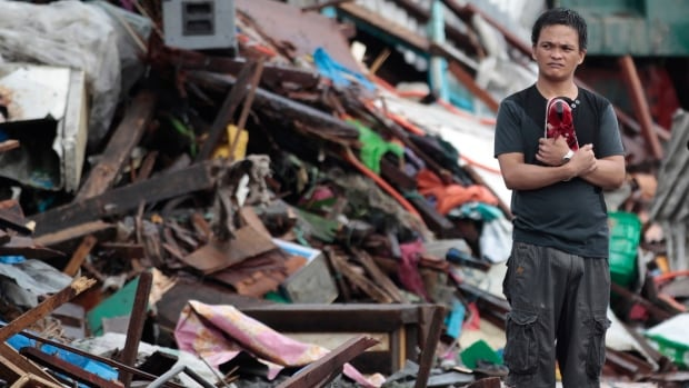 A resident looks at houses damaged by Typhoon Haiyan in the city of Tacloban in the central province of Leyte in the Philippines on Sunday.