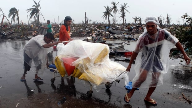 Residents transport a hospital stretcher filled with sacks of rice they looted past destroyed houses after Typhoon Haiyan battered the city of Tacloban in central Philippines.
