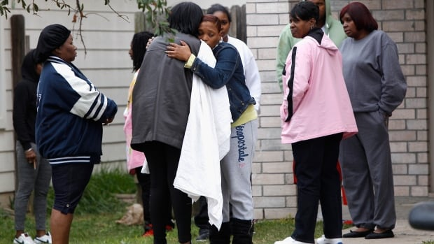 Family and friends console each other outside a home in Cypress, Texas, on Sunday after two people were killed and at least 22 others were injured when gunfire rang out at a large house party Saturday night.