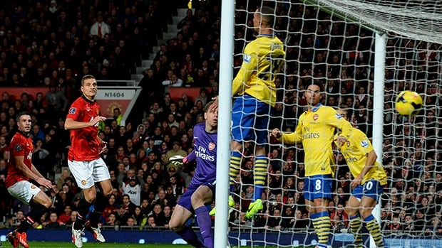Manchester United's Robin van Persie, left, scores against Arsenal in Manchester, northwest England, November 10, 2013.