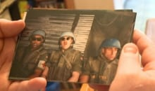 Paul Bornn flips through photos Bosnian war veteran