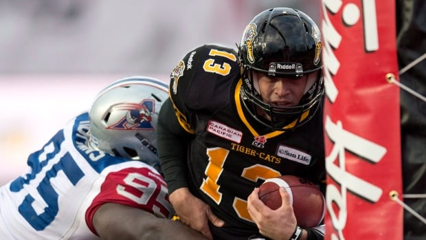 Hamilton Tiger-Cats quarterback Dan LeFevour runs in the game winning touchdown past Montreal Alouettes defensive tackle Moton Hopkins (95) during overtime East Division semifinal CFL action in Guelph, Ont., on Sunday, November 10, 2013.