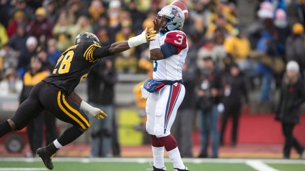 Montreal Alouettes quarterback Troy Smith tries to pass under pressure from Hamilton Tiger-Cats linebacker Jamall Johnson during first half East Division semifinal CFL action in Guelph, Ont., on Sunday, Nov. 10, 2013.