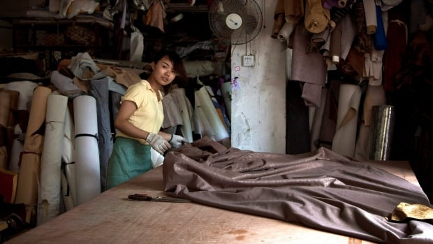 A worker lays out fabric at a local furniture manufacturing factory in Zhanjiang, China. More and more business owners are pushing back at Beijing's strongarming. (Andy Wong/Associated Press)