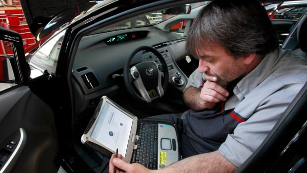 A diagnostic technician uses a laptop computer to diagnose and repair the brake system on a 2010 Toyota Prius. Canadian businesses are reporting a skills gap in IT workers.