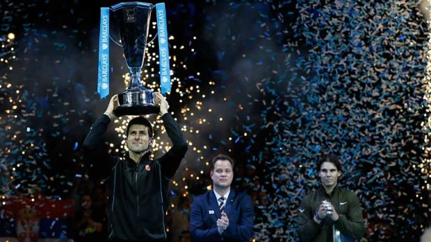 Novak Djokovic holds up the ATP World Tour Finals trophy as he poses for photographers after defeating Rafael Nadal at the O2 Arena in London on Monday.