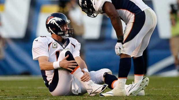 Denver Broncos quarterback Peyton Manning, left, holds his leg after being injured while playing the San Diego Chargers in the second half on Sunday in San Diego.