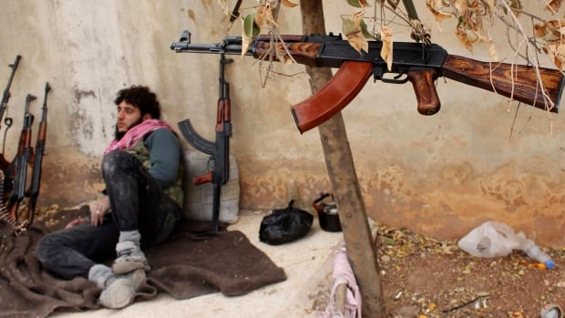 A fighter from the Tawhid Brigade, which operates under the Free Syrian Army, rests by the weapons of his fellow fighters near the 80th Brigade base in Aleppo Nov. 11. Syrian forces backed by Lebanese Hezbollah militants recaptured an army base in northern Syria from rebels on Sunday, the third day of heavy fighting for the strategic military target which has changed hands three times since Friday.