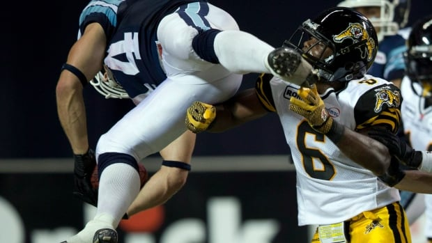 Toronto Argonauts running back Chad Kackert (left) dives over Hamilton Tiger-Cats defensive back Armando Murillo to score a touchdown during second half CFL action in Toronto on Saturday September 8, 2012. Kackert will miss the rest of the playoffs with a broken ankle.