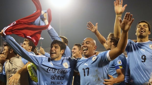 Uruguay players celebrate after winning their FIFA 2014 World Cup qualifier intercontinental playoff 1st leg match 5-0 over hometown Jordan on Wednesday in Amman.