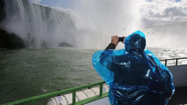 A tourist takes photos from the top deck of the Maid of the Mist in Niagara Falls, Ont., one of Canada's most popular tourist sites. Travel overal to Canada overall, however, is in decline, according to a new report.