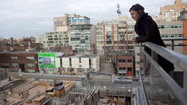 Condo owner Eva Kanovich looks onto a  neighbouring condo under construction from her balcony in downtown Toronto on Feb. 4,  2012.  A new report says there is an enduring trend toward living, working and playing in one neighbourhood close to transit