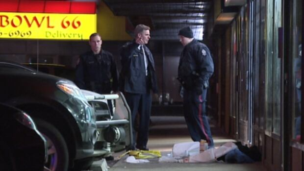 Police officers investigate one of two crime scenes in northeast Edmonton Thursday evening.