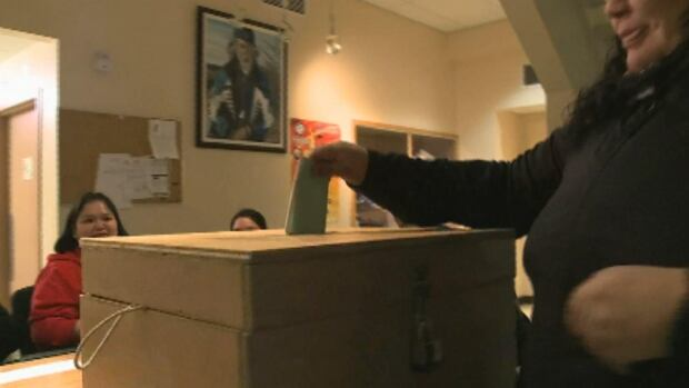 A woman casts her ballot at the band council office in Natuashish on Friday afternoon.