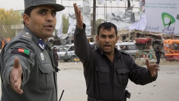 Afghan policemen rush to the scene after a powerful suicide vehicle bomb tore through the outskirts of Kabul. The deadly bomb targeted a site where thousands of elders are to gather next week to discuss a controversial security agreement with the United States.