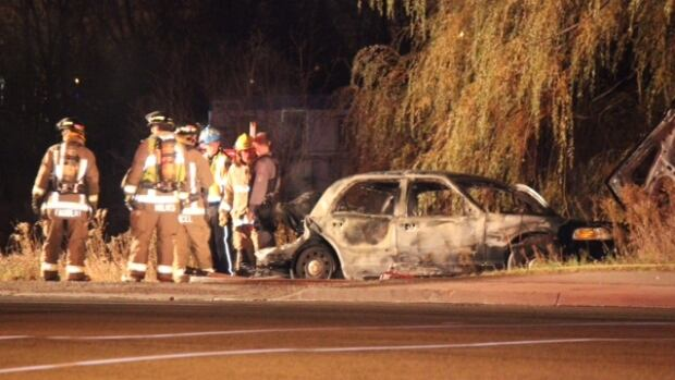 Firefighters stand near the wreckage of a car that caught fire after it was rear-ended by a transport truck in Mississauga early on Saturday morning.