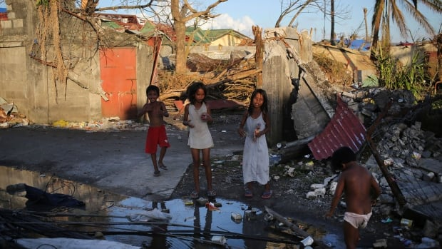 Survivors of Typhoon Haiyan stand along the debri strewn streets Nov. 16 in Tacloban city in the central Philippines.