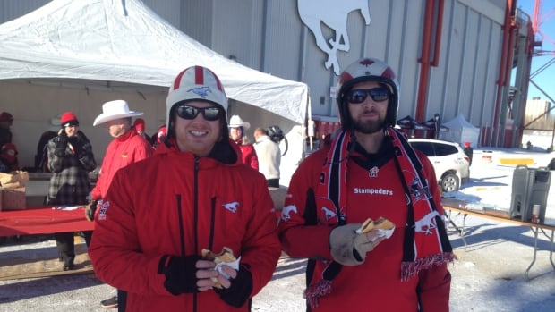 Calgary Stampeders fans Steve Luft, left, and Dan Towson chow down on pancakes and sausage at the team's pancake breakfast Sunday.