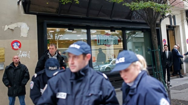Police officers stand outside Liberation newspaper office in Paris on Monday after a gunman opened fire in the lobby, wounding a photographer's assistant before fleeing. Fabrice Rousselot, editor of the daily newspaper Liberation said the 27-year-old victim was in serious condition.