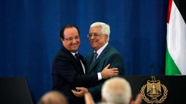 Palestinian President Mahmoud Abbas, right, and French President Francois Hollande hug during a joint press conference in the West Bank city of Ramallah on Monday. Hollande was in the region to meet with Palestinian and Israeli leaders as part of a U.S.-led process to restart peace talks between the two sides.