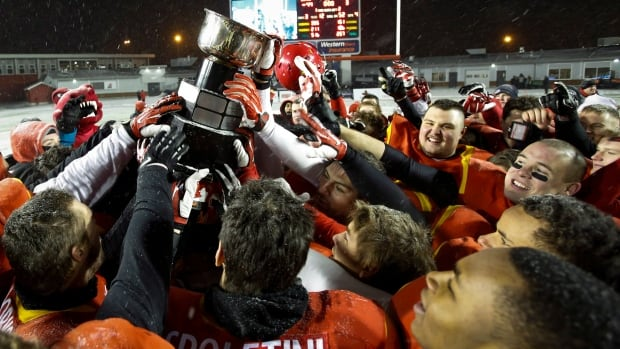 University of Calgary Dinos' celebrate winning the CIS Mitchell Bowl against the Western University Mustangs in Calgary Saturday.