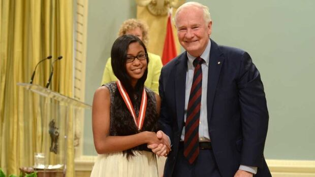 Kelsey Omaga, left, stands with Gov. Gen. David Johnston after receiving the Kayak Illustrated History Award at Rideau Hall on Tuesday.