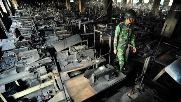 A Bangladeshi police officer walks past rows of burnt sewing machines in the burned out Tazreen garment factory in Savar, on the outskirts of Dhaka. The 2012 fire killed 112 workers. North American and European retailers have agreed to a safety inspection scheme.