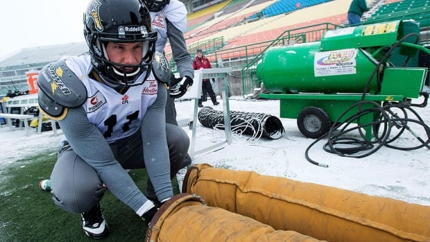 Tiger-Cats wide receiver Samuel Giguere warms his hands as he takes part in practice Wednesday in Regina. Many of his teammates got frostbite as the temperature felt like minus-28 C with the windchill.