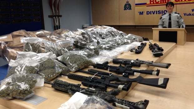 Yukon RCMP Cpl. Calista MacLeod stands with some of the cocaine, marijuana and firearms seized in a recent drug bust.