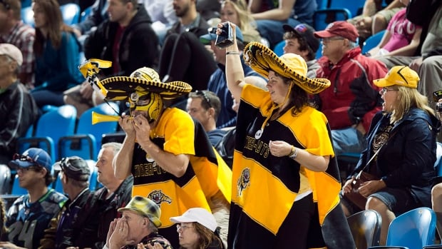 Hamilton Tiger-Cats fans cheers as their team plays the Montreal Alouettes in CFL action in Moncton, N.B. on Saturday, Sept. 21, 2013. Hamilton won 28-26.