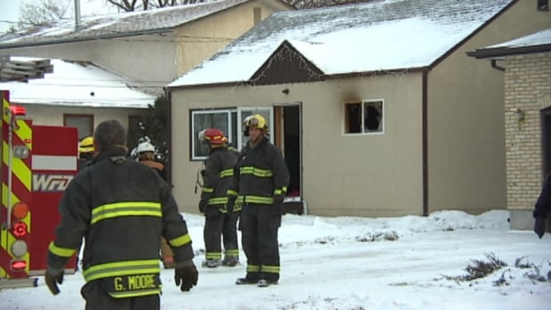 Winnipeg firefighters at the scene of a house fire on Hindley Avenue on Friday afternoon. One man died in the fire, according to police.