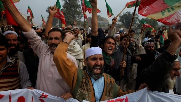 Thousands of people protesting U.S. drone strikes blocked a road in northwest Pakistan used to truck NATO troop supplies and equipment in and out of Afghanistan.