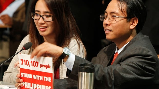 Philippine Climate Commissioner Naderev Sano, right, holds a sign during the closing session of the United Nations Framework Convention on Climate Change in Warsaw, Poland.
