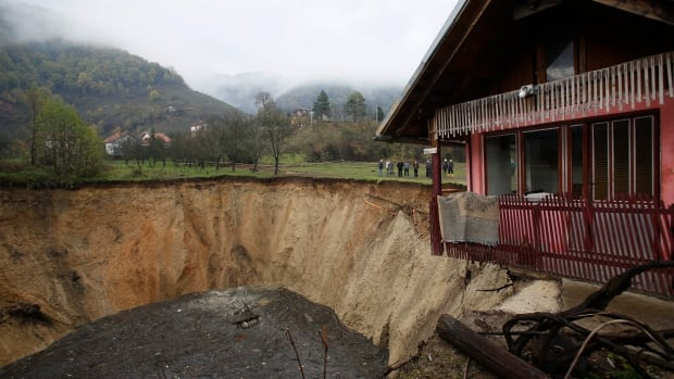 People gather around a huge sinkhole in Sanica, Bosnia-Herzegovina, that two weeks ago was a pond full of fish and algae. Scientists say it isn't uncommon for ponds and small lakes to disappear. This sinkhole may have been caused by drying underground waters or changes in soil drainage due to agricultural irrigation.