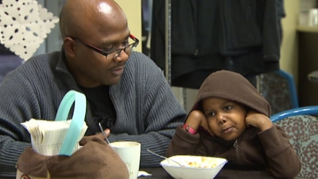 Boniface Mgonja and his daughter Michelle share a meal at Edmonton's Ronald McDonald House where the family is staying while Michelle undergoes treatment for leukemia. The family is looking for a new home.